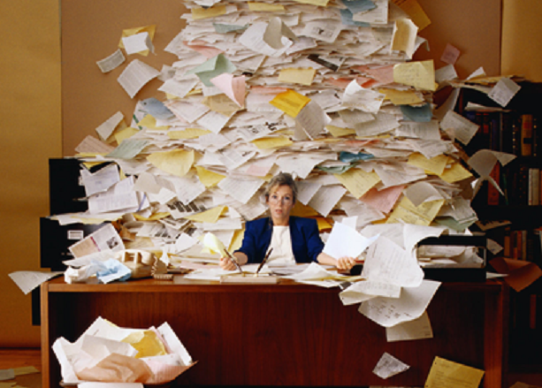 BUSINESSWOMAN-sitting-at-a-desk-with-a-large-pile-of-paper-by-Microsoft.png