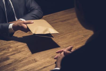 1578475444_90032718-un-homme-donnant-de-l-argent-de-pot-de-vin-dans-une-enveloppe-brune--un-autre-homme-d-affaires-.jpg.a74c690480c7395fe5383e3a45e59b46.jpg